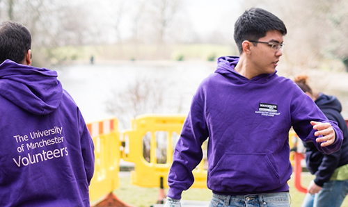Two students wearing purple hoodies, volunteering in a field