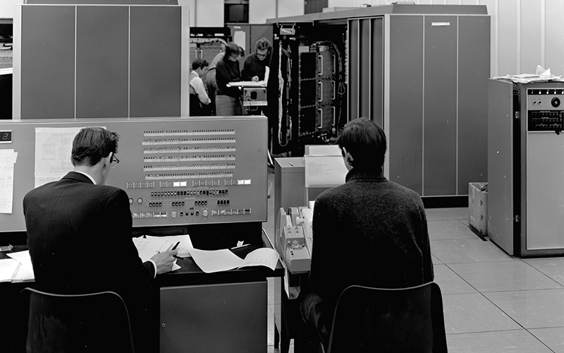 Black and white image of students working with the MU5 computer