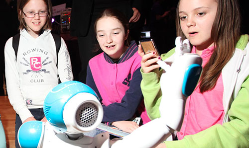 Three young pupils gazing at a robot