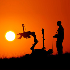 Man operating a robotic vehicle silhouetted against a sunset sky.