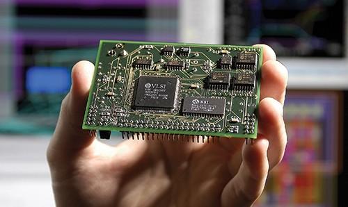 Hand holding green electronic cicruit board