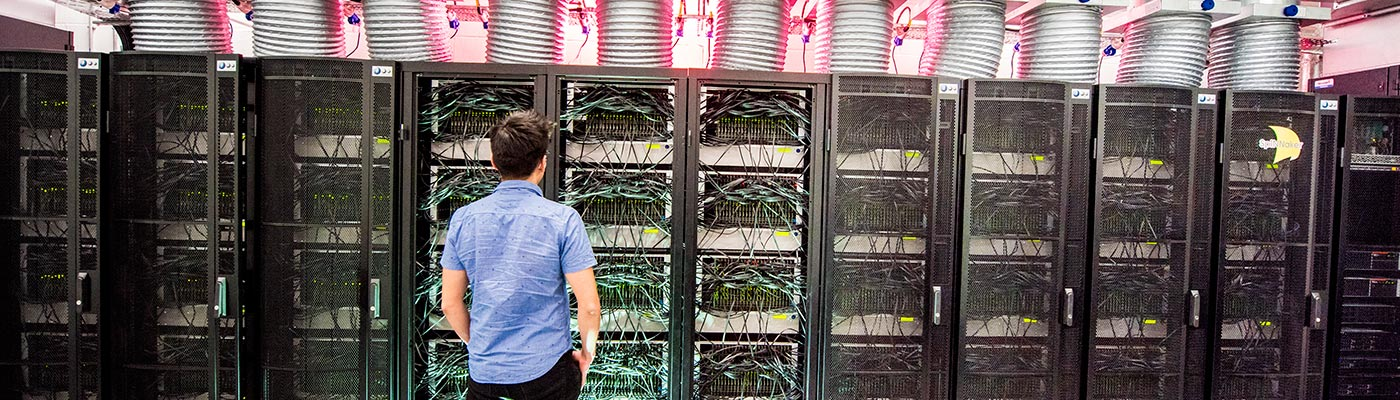 A male student standing in front of the Human Brain computer
