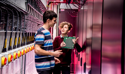Two students in discussion about a computer circuit board in a corridor
