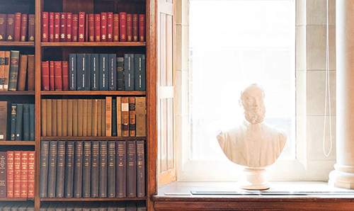 A bust in front of rows of different coloured books