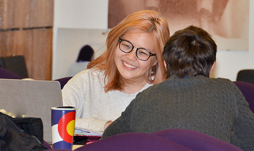 Female student smiling while in discussion at an event