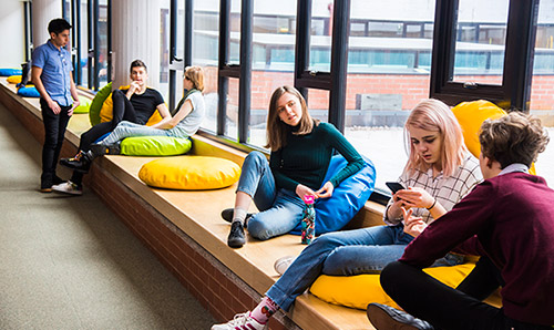 Group of students lounging on cushions in Kilburn Building